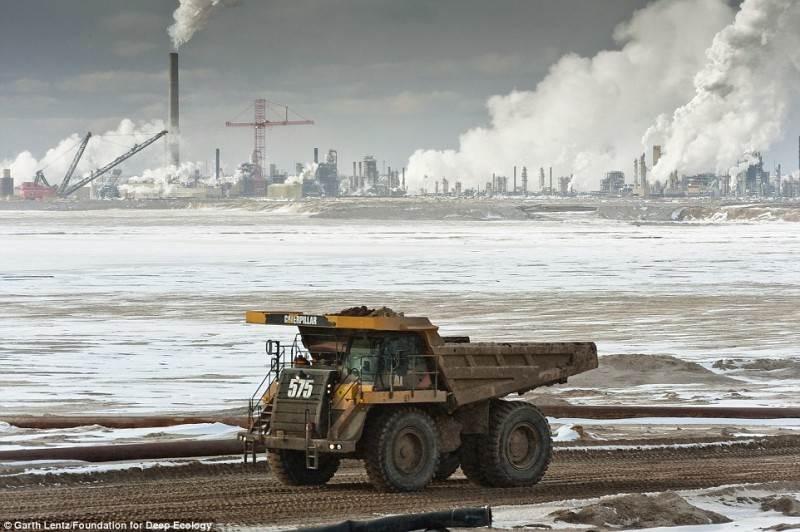 Didžiulis sunkvežimis veža perdirbti smėlį. Naftos prisisunkęs smėlis – ateities energijos šaltinis.